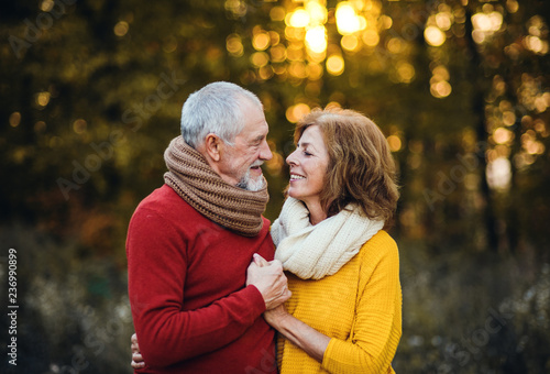 Leinwandbild Motiv A senior couple standing in an autumn nature at sunset, looking at each other.