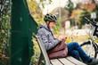 Leinwandbild Motiv A senior man with electrobike sitting on a bench outdoors in town, using smartphone.