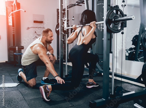 Fitness woman exercising with fitness trainer in gym. Personal fitness instructor.