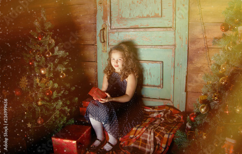 Foto Murales Happy little girl  decorate Christmas tree