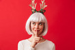 Quadro Cute woman isolated over red wall background wearing deer ears costume carnival showing silence gesture.