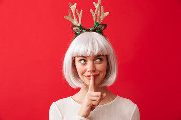 Cute woman isolated over red wall background wearing deer ears costume carnival showing silence gesture.