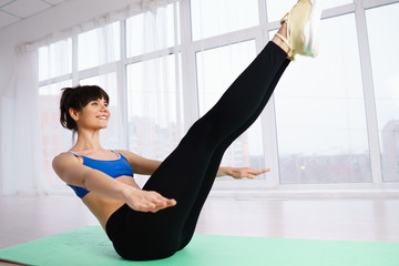 Healthy lifestyle, power, endurance, sport, fitness workout. Sporty woman doing static exercise in yoga studio