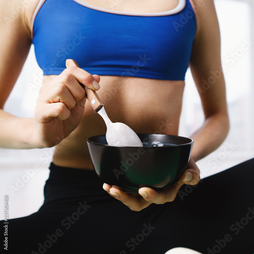 Foto Murales proper nutrition, diet, healthy lifestyle and sport. Young fit woman having light snack after workout. eating protein smoothie bowl