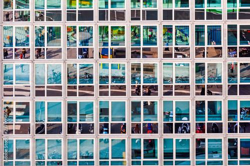 fasada budynku biurowego z odbiciem życia ulicy