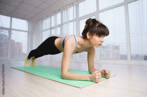 Naklejka Flexibility, health, good mood, active lifestyle, workout, harmony. fit sporty woman practicing yoga in studio doing plank exercise
