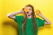 Happy young man holding oranges on a yellow background