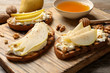 Leinwanddruck Bild - Toasted bread with tasty cream cheese and pear on wooden board