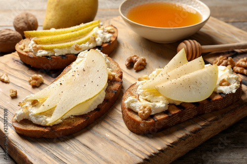 Leinwanddruck Bild Toasted bread with tasty cream cheese and pear on wooden board