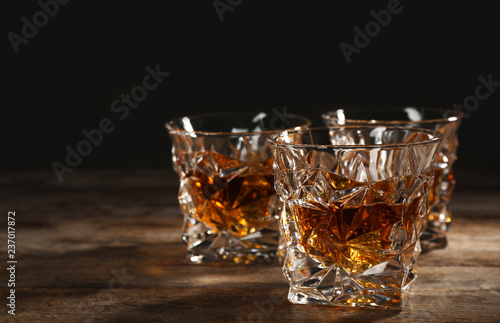 Leinwandbild Motiv Golden whiskey in glass with ice cubes on table. Space for text