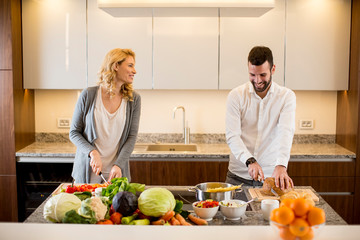 Beautiful young couple is talking and smiling while cooking healthy food in kitchen at home