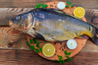 Leinwanddruck Bild - Raw carp fish with lemon, onion, pepper and parsley on cutting board on rustic wooden table