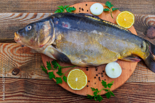 Raw carp fish with lemon, onion, pepper and parsley on cutting board on rustic wooden table - 237025630