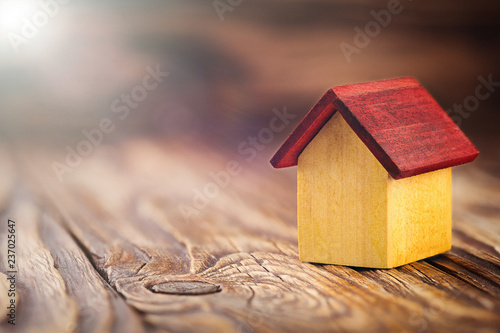 Leinwanddruck Bild Real  estate concept with small toy wooden house on wooden background. Idea for real estate concept, personal property and family house.