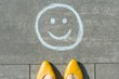 Leinwanddruck Bild - Symbol of happy smiley drawn on the asphalt and woman feet