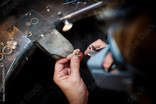 Jeweler saws at a gold ring in authentic jewellery workshop © photoflorenzo