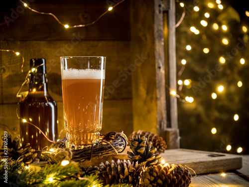 Leinwanddruck Bild Beer in glass on wooden background with Christmas lights and pine cones