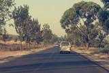 Mini bus driving along newly built road across savannah. © anzebizjan