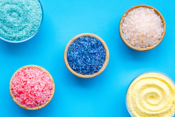 Spa salt background. Colorful spa salt in bowls on blue background top view. Yellow, turquoise, pink, purple spa salt © 9dreamstudio