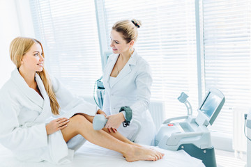 Professional beautician doing laser epilation on legs of attractive caucasian woman in white bathrobe in beauty clinic. Hair removal cosmetology procedure. Laser epilation and cosmetology.
