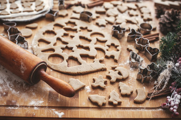 Making christmas gingerbread cookies. Dough with metal cutters on rustic table with wooden rolling pin, cinnamon ,anise, cones, christmas decorations. Atmospheric stylish image