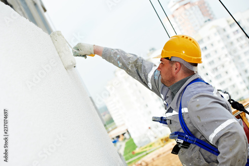 Plakat builder worker painting facade of building with roller