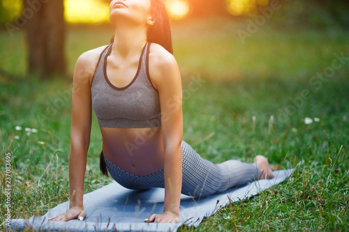 Fototapeta Young beautiful woman practicing yoga in the green park. Wellness concept. Calmness and relax, woman happiness.