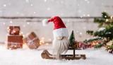Kleiner Weihnachtsmann sitzt auf seinem Schlitten und wünscht frohe Weihnachten