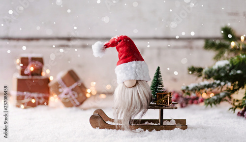 Kleiner Weihnachtsmann sitzt auf seinem Schlitten und wünscht frohe Weihnachten - 237086459