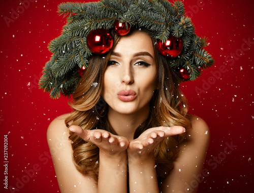 Leinwanddruck Bild Beautiful woman with Christmas spruce fir wreath with cones and new year decoration red balls