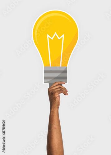Leinwandbild Motiv Hand holding a light bulb cardboard prop