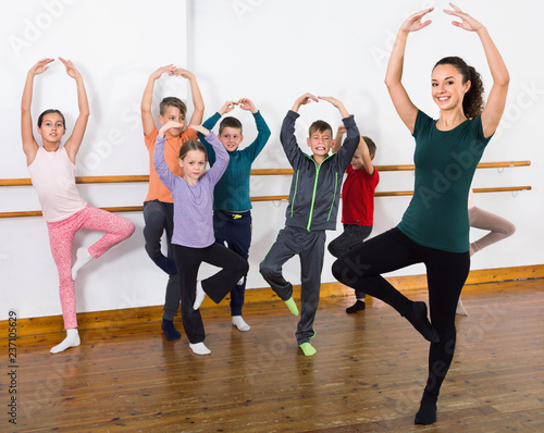 Young ballet dancers exercising in ballroom