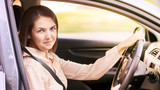 Young woman in car. Ride instruction. Automobile loan