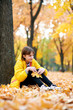 Sad teen girl sits near tree in autumn park. Bright yellow leaves and trees.