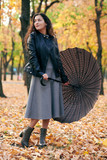 Woman with umbrella posing in autumn park. Bright yellow leaves and trees. - 237113824