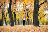Happy teen girl is running in autumn park with big maple's leaf. Bright yellow leaves and trees. - 237113894