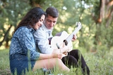 young couple sitting in the forest and playing guitar, summer nature, bright sunlight, shadows and green leaves, romantic feelings - 237114016