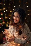 young girl is in christmas lights and decoration, dressed in white, fir tree on dark wooden background, winter holiday concept - 237114079