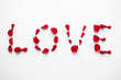 valentines day and romantic concept - word love made of red rose petals on white background
