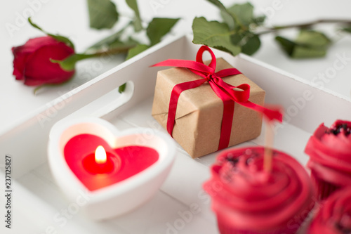Leinwanddruck Bild valentines day and sweets concept - close up of gift box, cupcakes with red buttercream frosting, heart shaped burning candle on tray and rose
