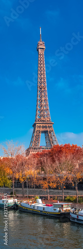 Paris, Eiffel tower in autumn, panorama with red trees and houseboats in the Seine