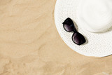 summer holidays and vacation concept - straw hat and sunglasses on beach sand