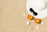 vacation, travel and summer concept - two glasses of aperitif cocktails with ice cubes, sun hat, sunglasses and seashells on beach sand