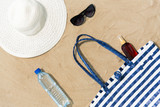 vacation, travel and summer concept - beach bag, sunscreen, sunglasses and hat on sand