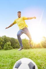 Mann spielt Fußball auf Wiese