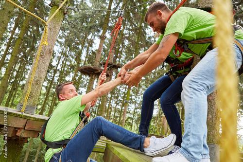 Leinwandbild Motiv Team hilft Mann beim Klettern im Hochseilgarten