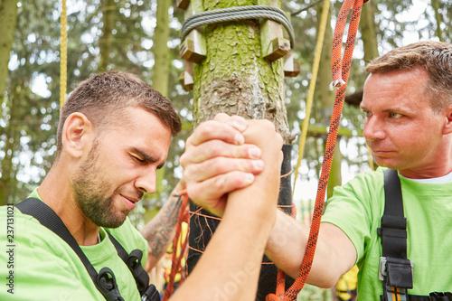 Leinwandbild Motiv Männer im Hochseilgarten feiern ihren Erfolg