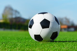 Classic soccer ball lying on the bright green grass on the football field in the background of the stands for the fans at the sports stadium close-up in a large sports center for football players