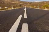Asphalt road leads into the mountains. Closeup asphalt road - 237136605