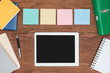 Quadro top view of four sticky notes and digital tablet with blank screen on wooden office desk